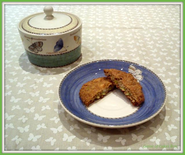 Cookie de avena, pistachos y chocolate blanco partida por la mitad.