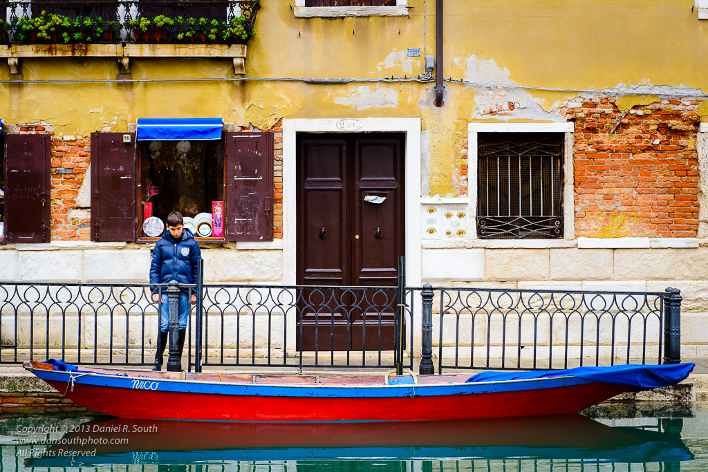 a photo of a boy and a boat named nico in venice italy by daniel south