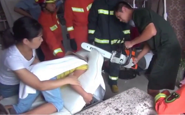 A boy with his head stuck in the massage table, is released using chainsaw