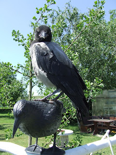 A crow stands upright on a statue of a bird.