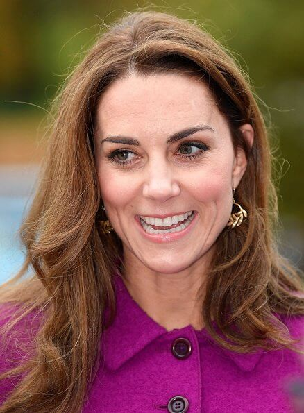 Kate Middleton wore Oscar de la Renta burgundy jacket and pleated skirt, Zoraida gold earrings, and she carred Aspinal of London clutch