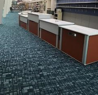 Combined Information and Circulation service desks, showing new carpeting