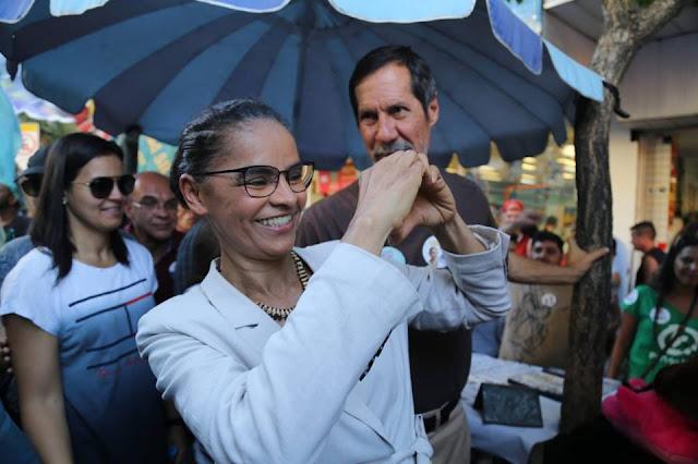 Foto de Marina Silva fazendo coração com as mãos, com seu vice Eduardo Jorge ao lado.