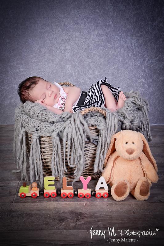 portrait bébé couché dans panier en osier avec plaid en laine gris