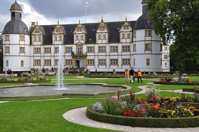 Das Paderborner Schloss Neuhaus von der Gartenseite. Im Vordergrund ein Springbrunnen.