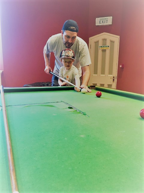 Daddy and son playing snooker