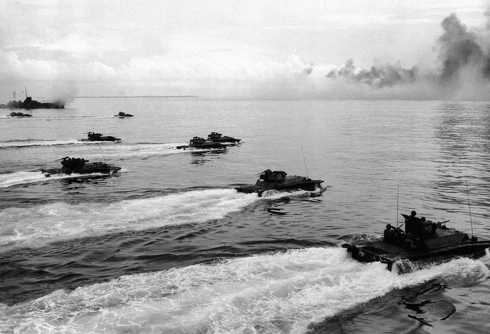 As a rocket-firing LCI lays down a barrage on the already obscured beach on Peleliu, a wave of Alligators (LVTs, or Landing Vehicle Tracked) churn toward the defenses of the strategic island September 15, 1944. The amphibious tanks with turret-housed cannons went in in after heavy air and sea bombardment. Army and Marine assault units stormed ashore on Peleliu on September 15, and it was announced that organized resistance was almost entirely ended on September 27.