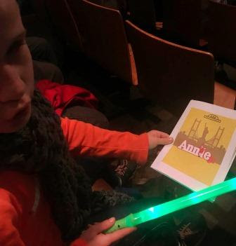 Girl with green light saber and Annie JR programme in hand