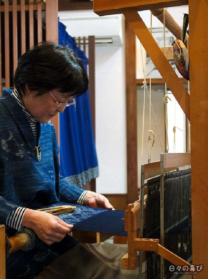 artisan fabriquant un tissu kasuri sur son métier à tisser