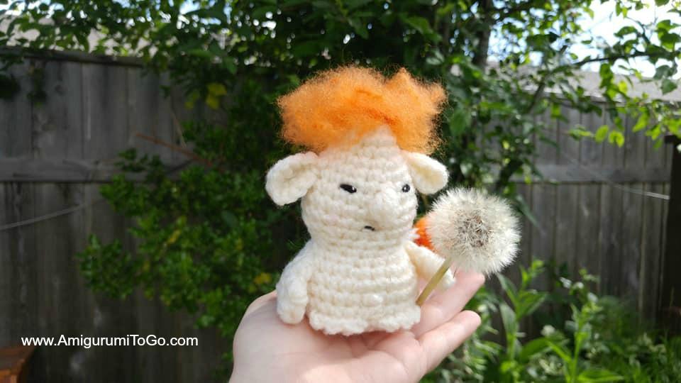 crochet troll inside a hand with a dandelion puff