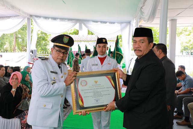 Sekda Asahan Taufik ZA menyerahkan penghargaan kepada camat.