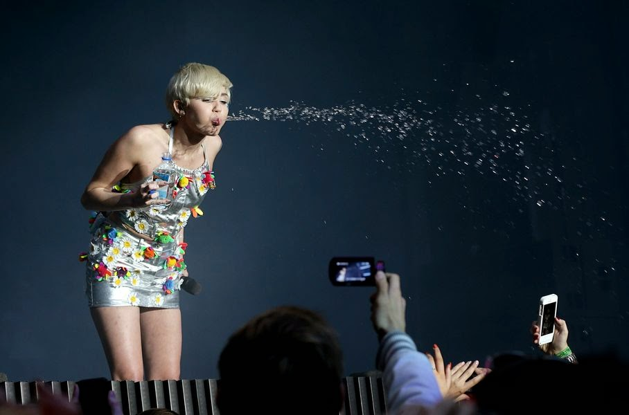 Miley Cyrus spits water onto her fans during Capital FM's Summertime Ball at Wembley Stadium in London, Saturday, June 21, 2014.