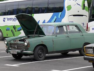 Kuba, Havanna, Parque Céspedes, uralter grüner Peugeot 404 mit hochgeklappter Motorhaube.