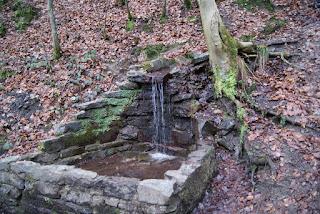 Ein kleiner, quadratischer Quellbrunnen steht an einem Hang. Wasser fließt vom Hang in den Brunnen.