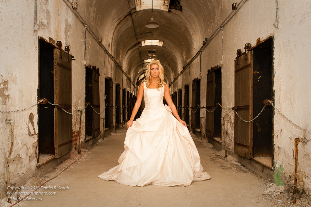 a photo of a model in a wedding dress in an old prison
