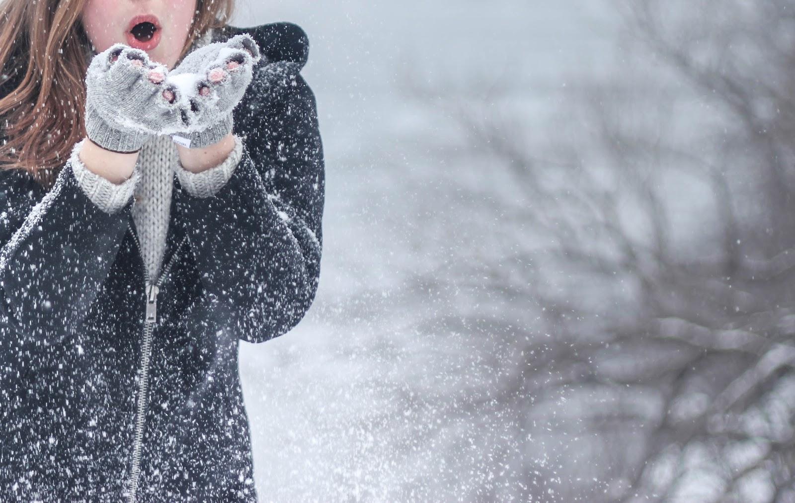 両手を口の前に揃えながら降る雪を吹き飛ばす女性