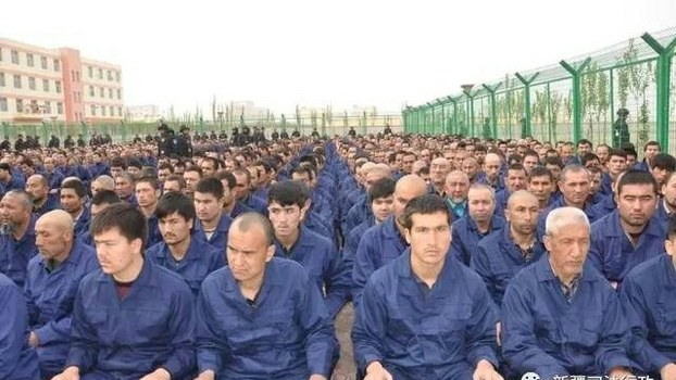 Image Attribute: A photo posted to the WeChat account (@RianThum) of the Xinjiang Judicial Administration shows Uyghur detainees listening