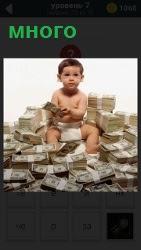 Ребенок сидит на большом количестве денежных пачек, которых много вокруг разбросано