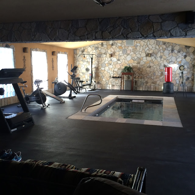 Man Cave with fitness and boxing equipment and an inground Endless Pools swimming machine