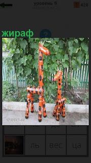 На асфальте стоят два игрушечных жирафа пятнистые оранжевого цвета