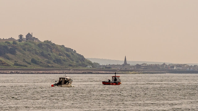 Photo of two small fishing boats with Maryport in the background