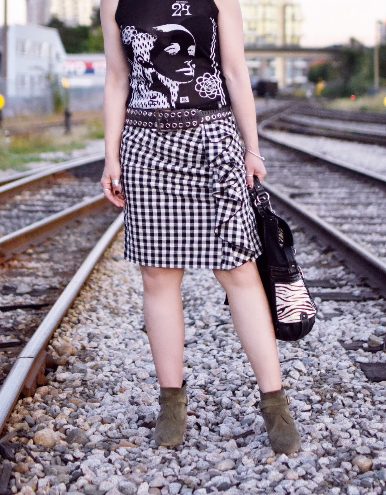 Monika Faulkner outfit inspiration - black and white graphic tank top and gingham skirt, brown grommet-embellished belt, olive suede booties, zebra-patterned satchel