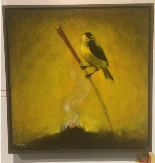 "The Caller of the Morning Prayer, by Dale Auger. Seen at Borealis Gallery ""The Dream We Form By Being Together"" exhibit. Photo by rob g. Image of yellow and black bird, perched on a stick, above smoking smudge"