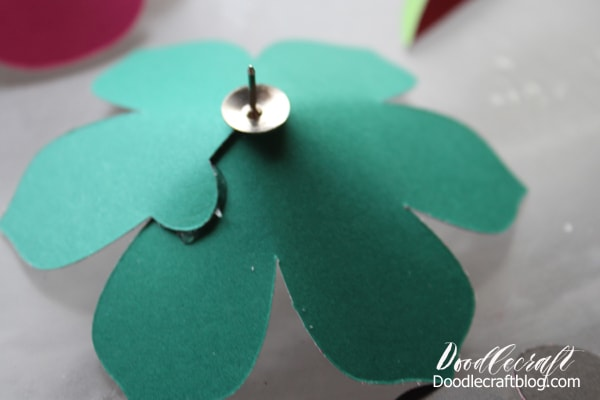 Thumbtack hot glued to the backside of a 3D paper flower to adhere it to a letterboard.