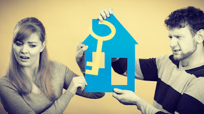 A couple holding a cut-out of a house. They appear apprehensive about moving in together.