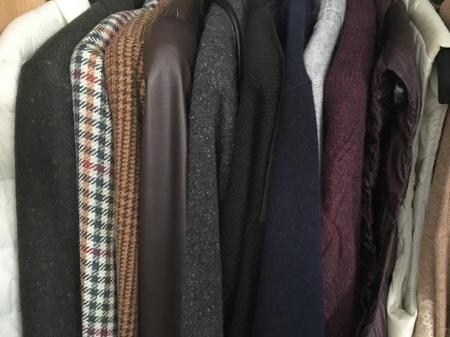 jackets and sweaters hanging in a closet