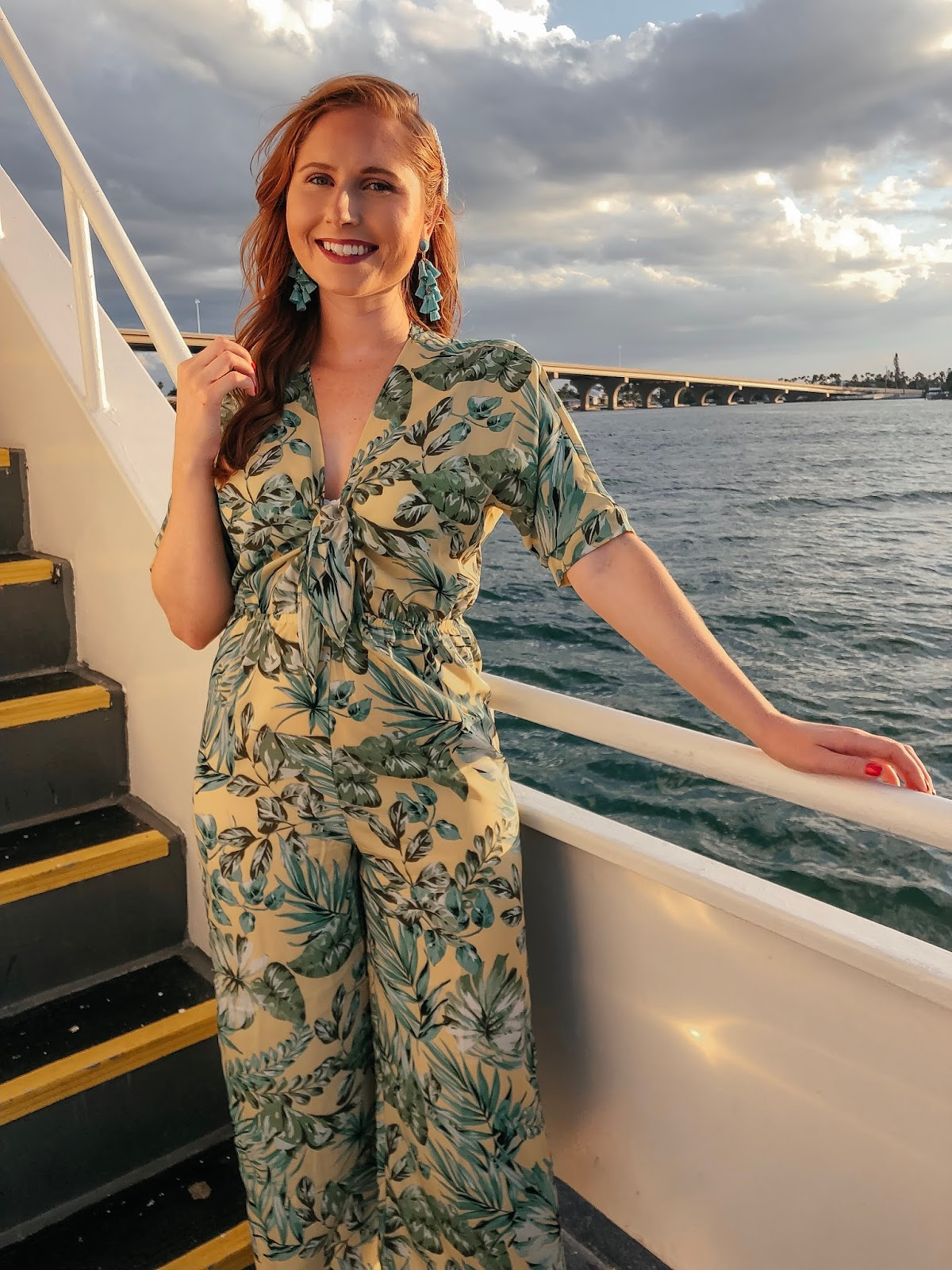 amanda burrows, blogger at affordable by amanda, is wearing a yellow and green palm print jumpsuit with a tie detail from Bealls Outlet. She is onboard of the Starlite Cruise that leaves from St. Pete Beach, Florida
