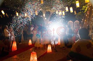 flower shower confetti blast on bride and groom arrival for beach wedding kerala