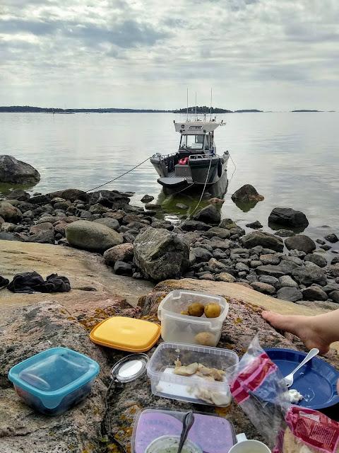 Kivikkoinen ranta, jolle laitettu eväät. Vene narussa taustalla.
