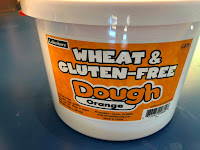 container of orange wheat and gluten-free dough