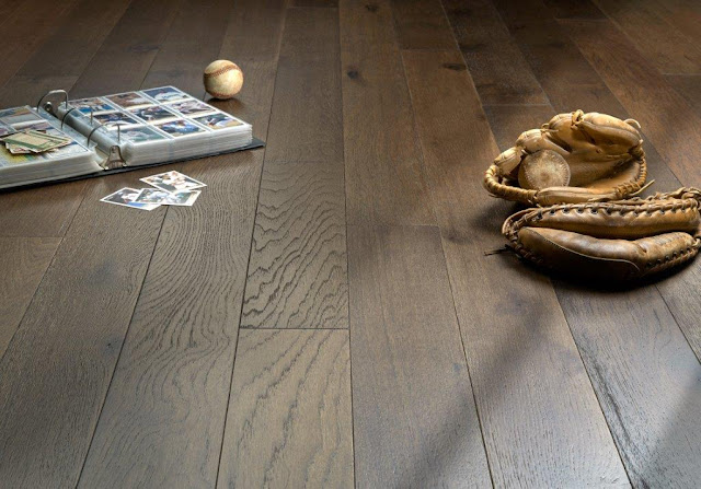 A close up look at this hardwood floor with a baseball mitt and card collection