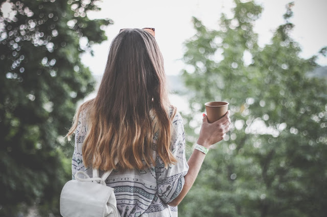 light haired woman's back facing us holding a latte looking drink in right hand