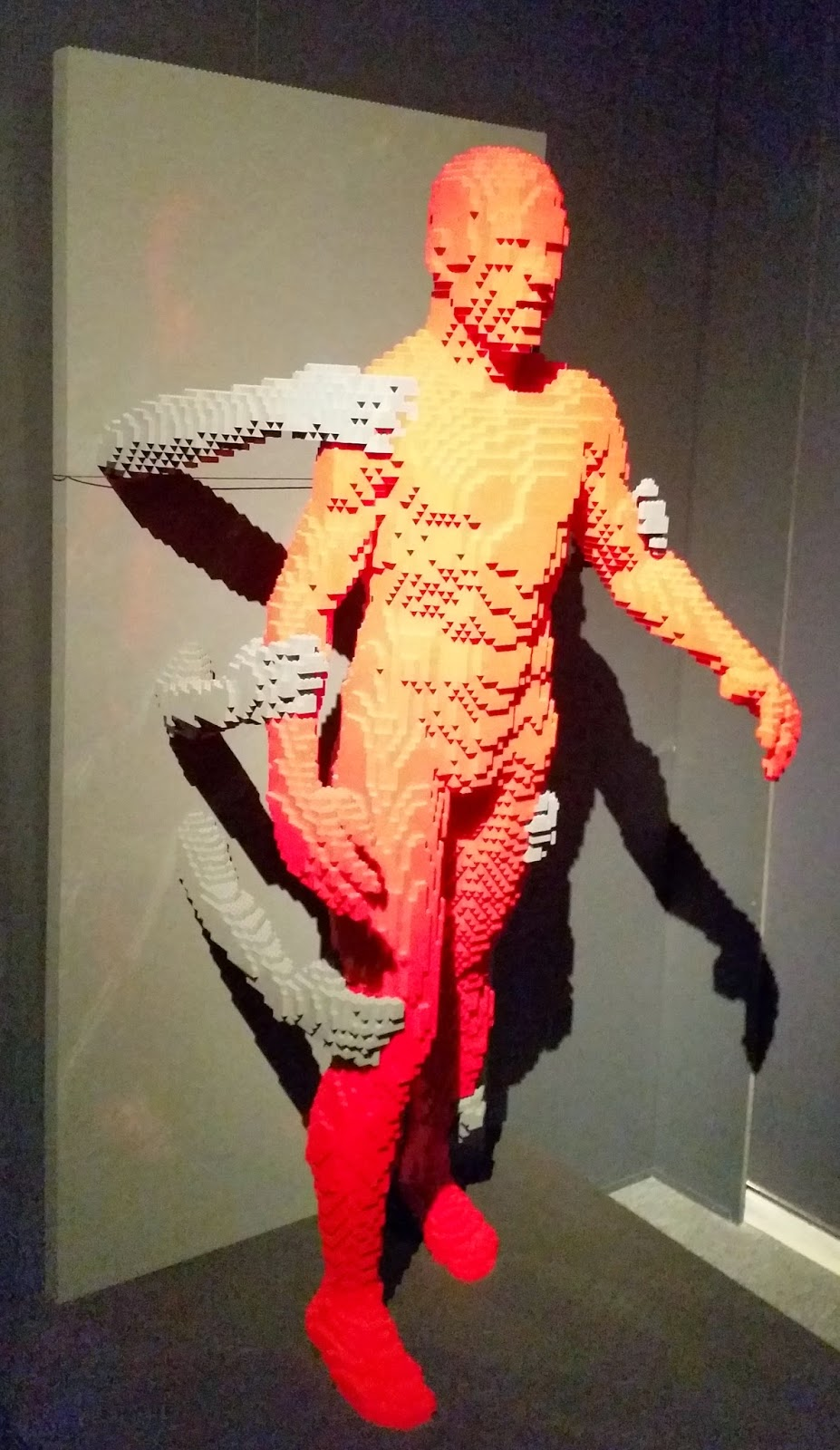 Lego man being held back by hands