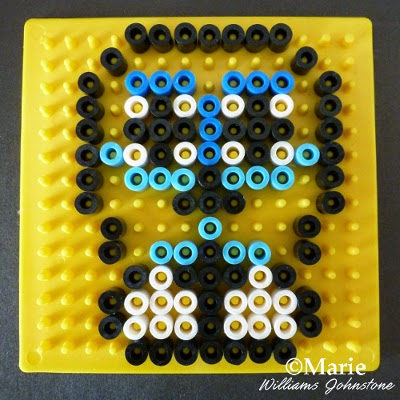 Yellow pegboard with design in black, white and blue colors