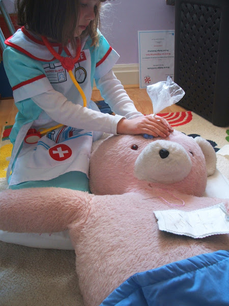 girl nurses her teddy bear