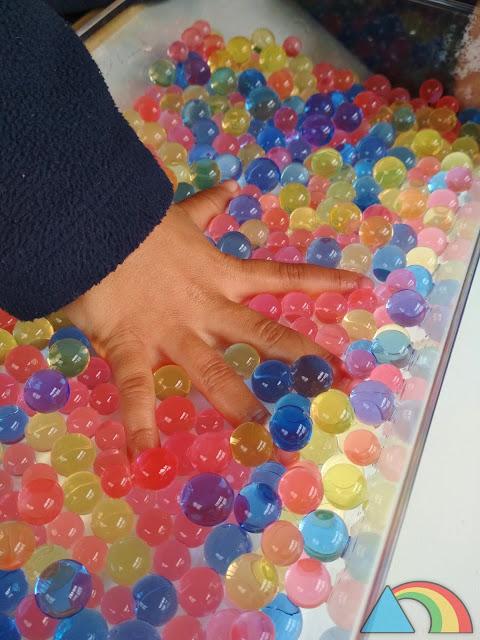Mano sumergida en recipiente lleno de bolas de gel o water beads de colores