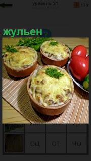 На столе стоят несколько тарелок с приготовленным жульеном и овощами