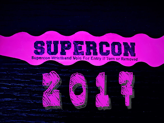 Supercon writstband on a black background and the year, 2017, below.