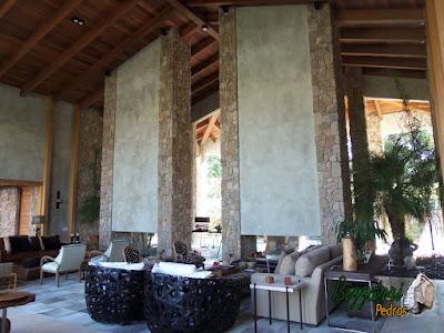 Parede de pedra, com pedra moledo, tipo chapada com cantos, nessa cor de pedra cinza mesclado em sala de estar com jardim de inverno em residência em Piracaia-SP.