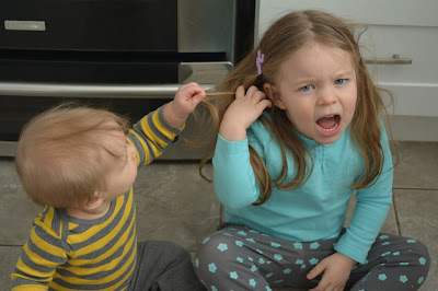 baby pulling toddler's hair