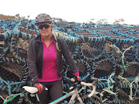 woman in front of lobster pots