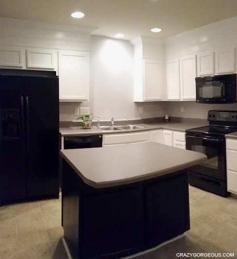 oak cabinets painted white - dark island and appliances.