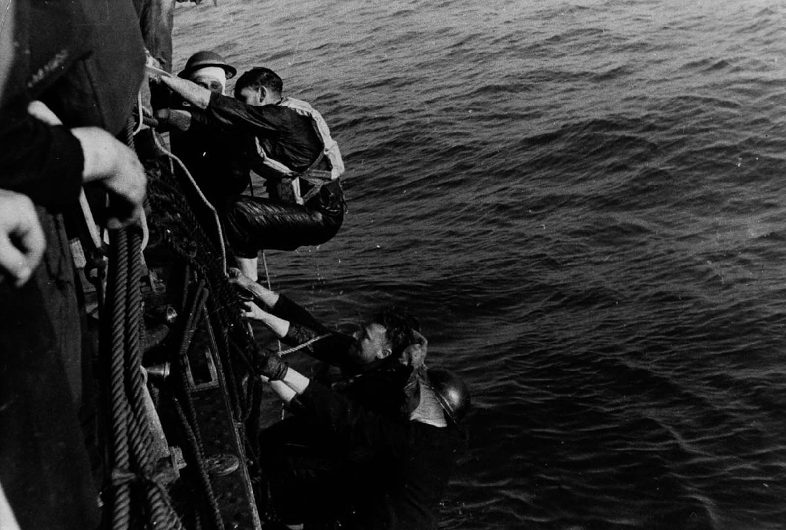 A British ship rescues soldiers from a landing craft sunk during the evacuation.