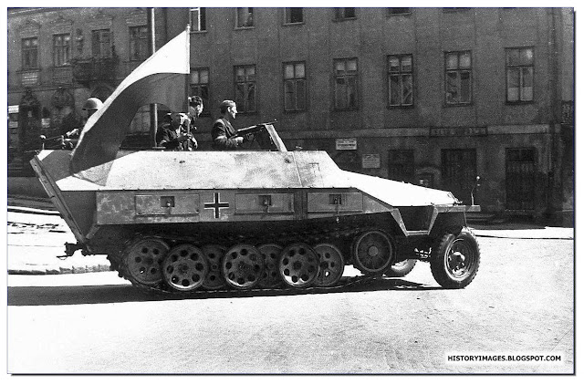 Armia Krajowa fighters ride  captured German armored carrier streets  Warsaw August 1944 uprising