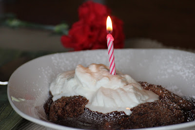 chocolate cake in a white bowl with whipped cream and a candle