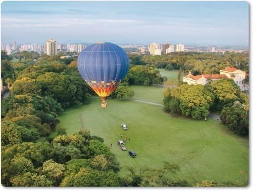 Paisagem de campos verdes, ao longe uma cidade e um lindo balão que se afasta no alto céu.